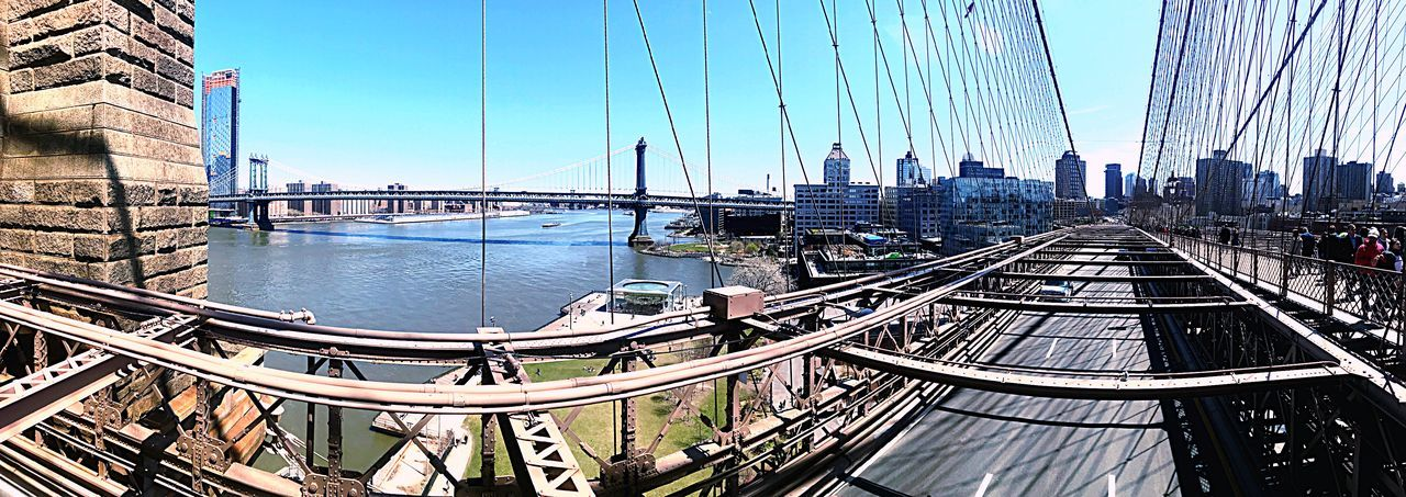 Panoramic view of suspension bridge and buildings against sky