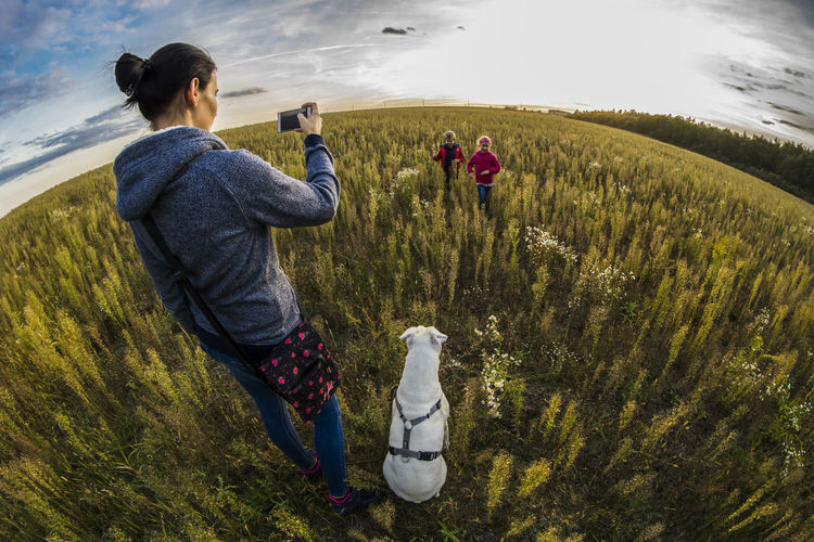 Fish-eye lens view of mother photographing children running on field