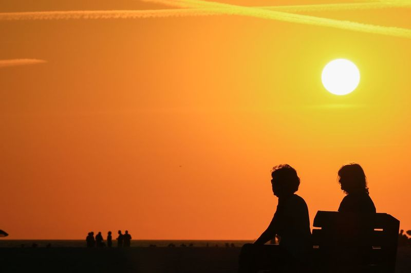 Sunset Silhouette Orange Color Sky Men Real People Group Of People Nature Lifestyles Beauty In Nature Leisure Activity Women Togetherness Adult People Scenics - Nature Land Sitting Copy Space Sun Outdoors Couple - Relationship Looking At View