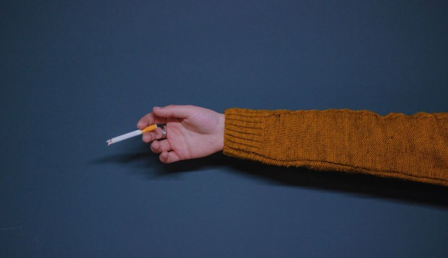 Close-up of hand holding cigarette over gray background