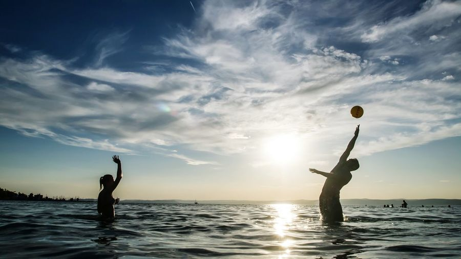 Friends Playing With Beach Ball In Sea During Sunny Day