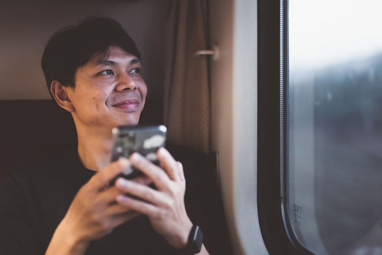 Smiling man using mobile phone by window in train