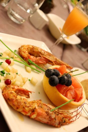 Close-up of shrimps and fruit with drink on table