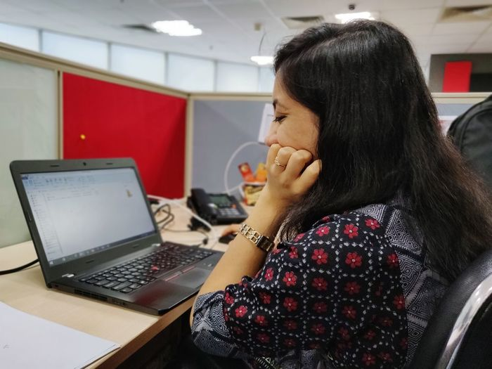 Side view of businesswoman using laptop while sitting on table at office