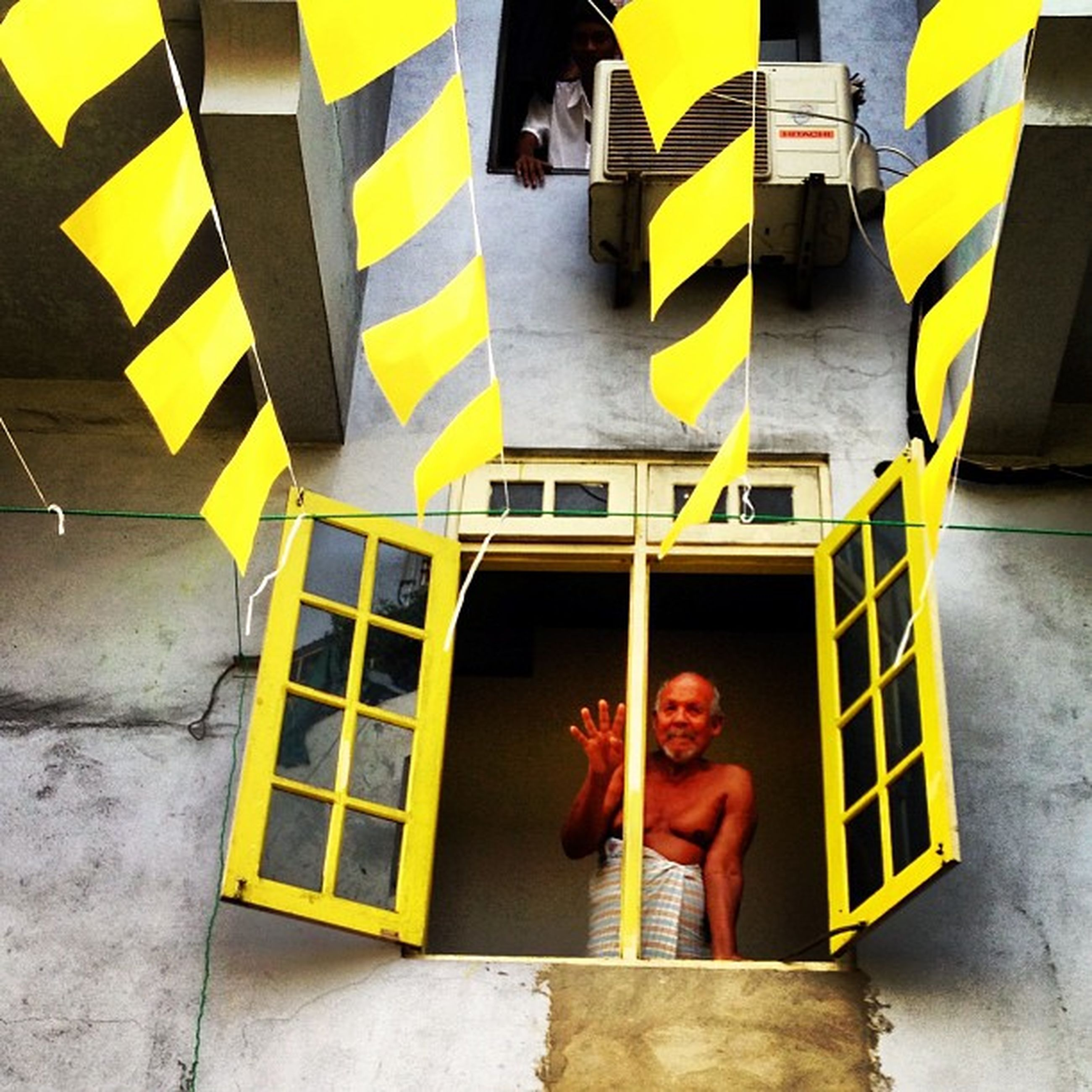 yellow, built structure, lifestyles, architecture, building exterior, wall - building feature, holding, standing, leisure activity, person, front view, casual clothing, art, three quarter length, creativity, day, outdoors, childhood