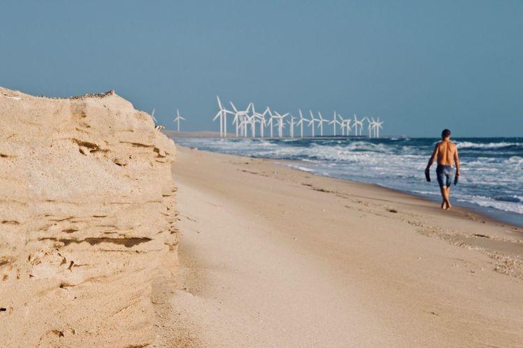 Rear view of shirtless man walking at beach against windmills