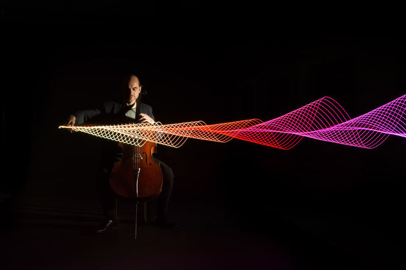 Full length of musician playing cello by light painting against black background