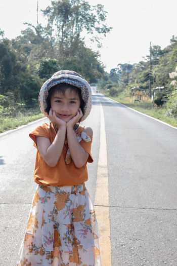 Portrait of cute girl standing on road
