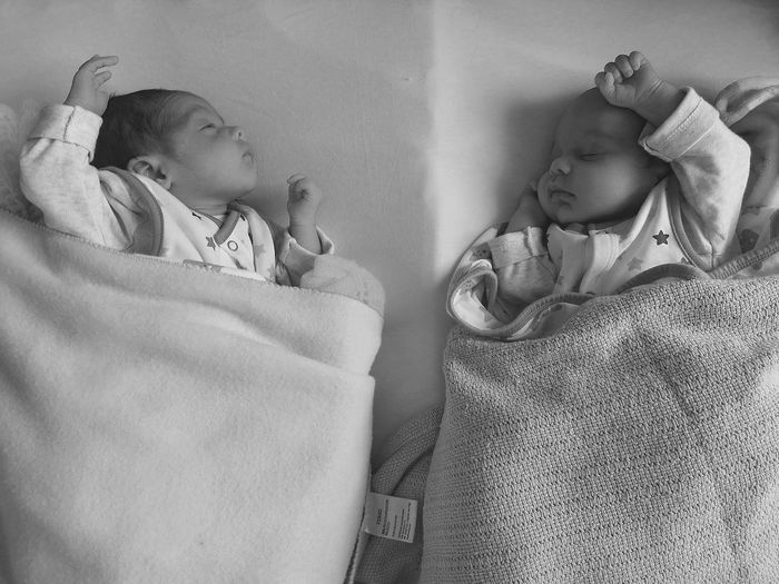 Directly above shot of newborn brothers sleeping on bed