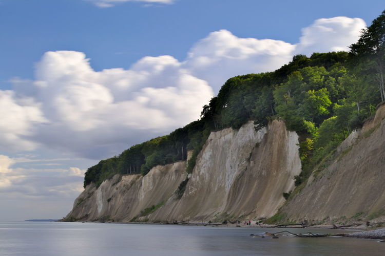 Scenic View Of Cliff At Sea Shore Against Sky