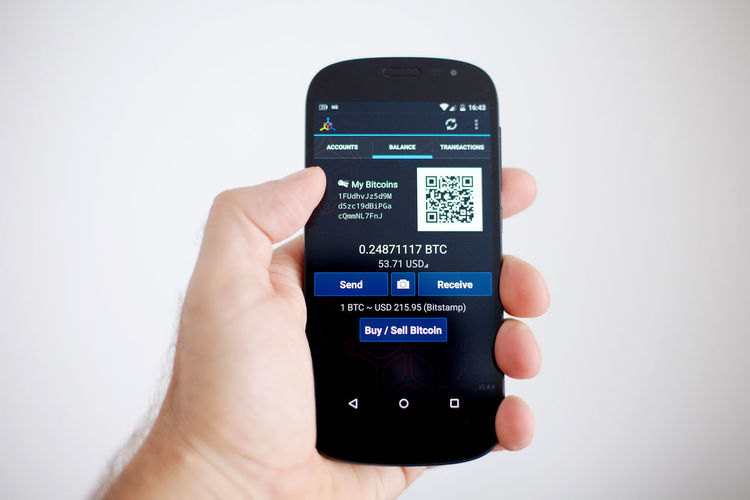 A hand holding a smartphone with a bitcoin wallet app on the screen. Bitcoin Bitcoin Wallet Bitcoin Wallet App Blockchain Communication Digital Display Human Hand Mobile Phone Smart Phone Technology Touch Screen Wallet App