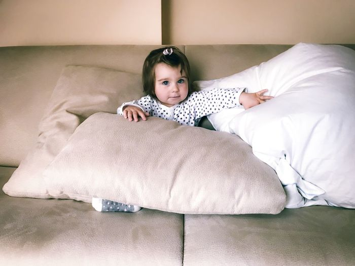 Full length of cute baby resting on bed at home