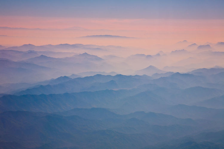 Scenic View Of Foggy Mountains At Sunrise