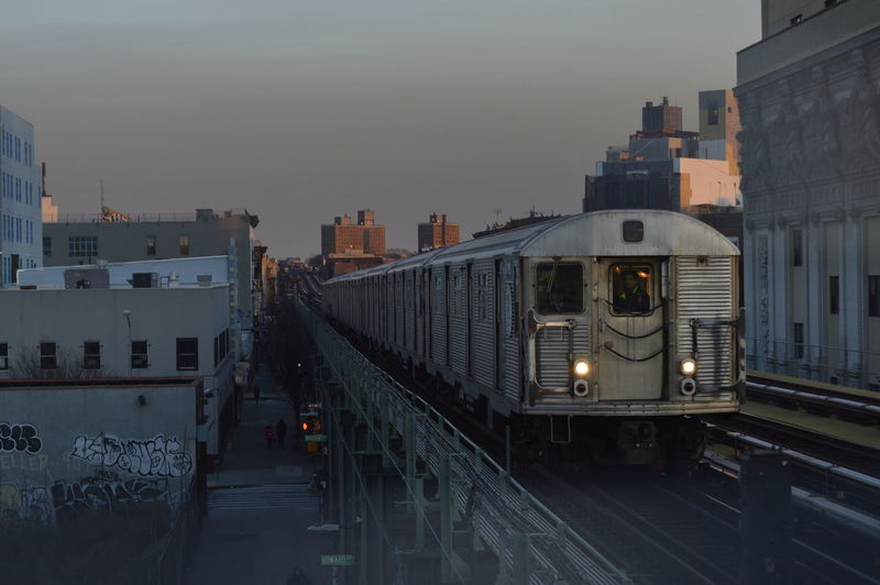 Train in city against sky at dusk