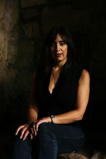 Portrait Of Mature Woman Sitting On Chair Against Wall