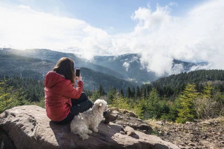 Rear view of woman with dog on mountain