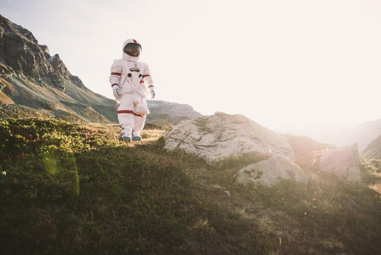 Full length of astronaut standing against sky