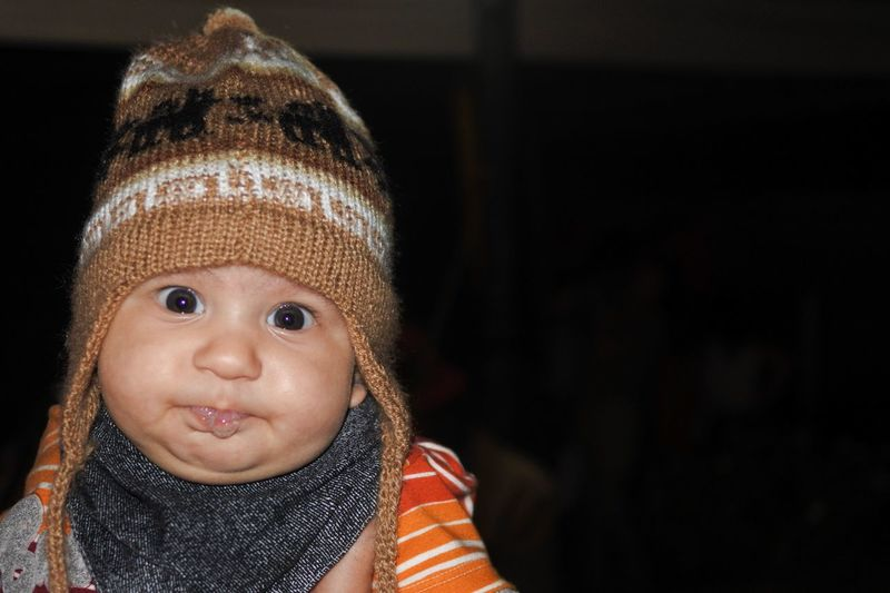 Close-up portrait of baby wearing knit hat against black background