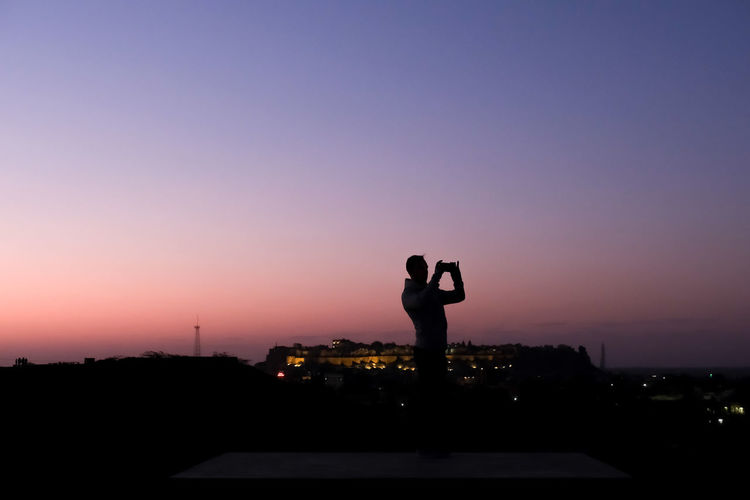 Silhouette man taking photos of jaisalmer during sunrise with smartphone