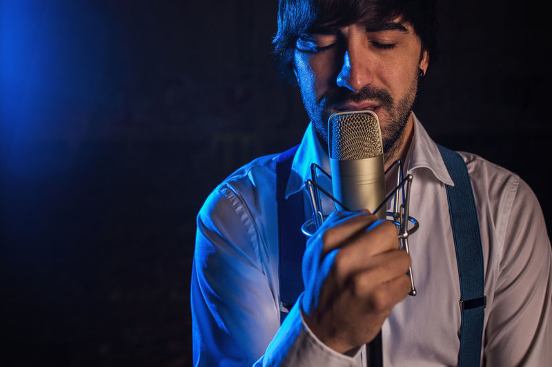 Close-Up Of Man Singing While Holding Microphone Over Black Background