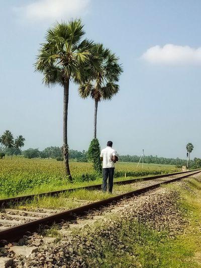 Rear View Of Man Walking On Railroad Track