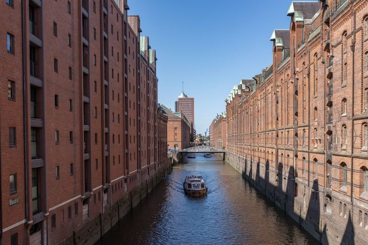Canal amidst buildings in city against clear sky