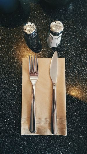 High angle view of table knife and fork on napkin at table