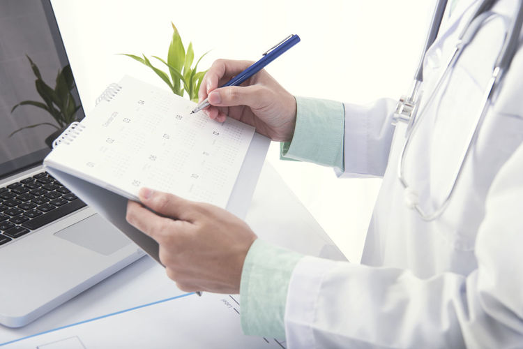 Midsection of doctor writing on calendar against white background