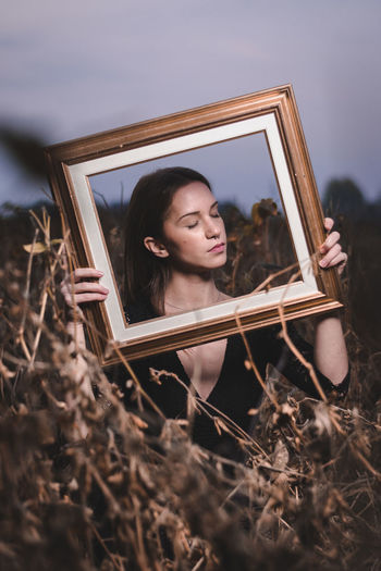 Close-up of young woman holding picture frame while standing on field against sky