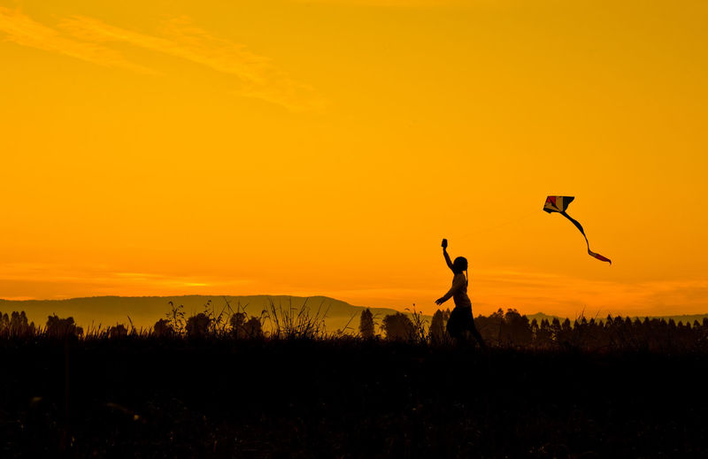 Silhouette Girl playing kite in the field. At sunrise Arms Raised Beauty In Nature Copy Space Environment Field Human Arm Land Landscape Leisure Activity Lifestyles Men Nature Orange Color Outdoors People Real People Scenics - Nature Silhouette Sky Sunset Tranquil Scene Tranquility