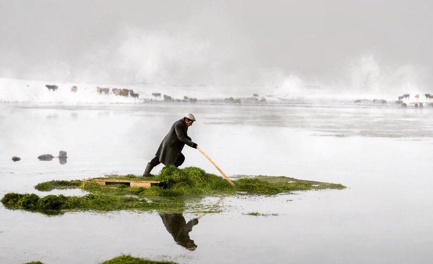Man standing on diving platform in lake