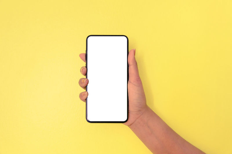 Midsection of person using smart phone against yellow background