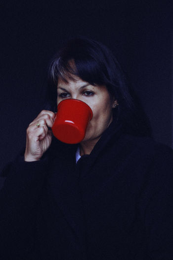 Coffee, 2017 Coffee Winter Adult Black Background Casual Clothing Cozy Dark Front View Hairstyle Headshot Holding Hot Drink Human Face Indoors  Leisure Activity Lifestyles Looking Looking At Camera One Person Portrait Real People Red Studio Shot Young Adult Young Women