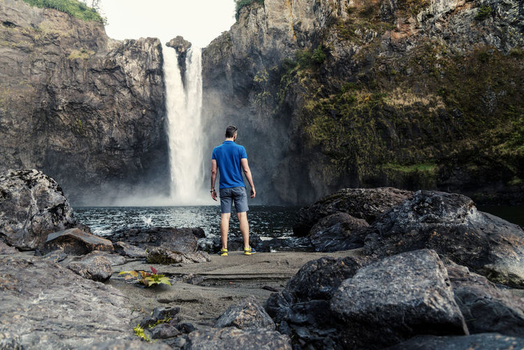 Rear view of mature man looking at waterfall while standing on rock