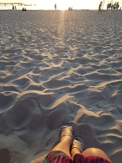 Relaxing lady s legs and feet at sunset time on misdroy beach with view towards water Line. .. Low Section Beach Water Sand Human Leg Shoe Personal Perspective Sky Human Feet Shore Sandy Beach Ocean Calm Sandal Feet Human Foot Foot