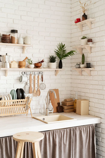 Rustic kitchen interior with brick wall and white wooden shelves