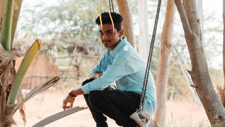 Portrait of young man sitting on swing