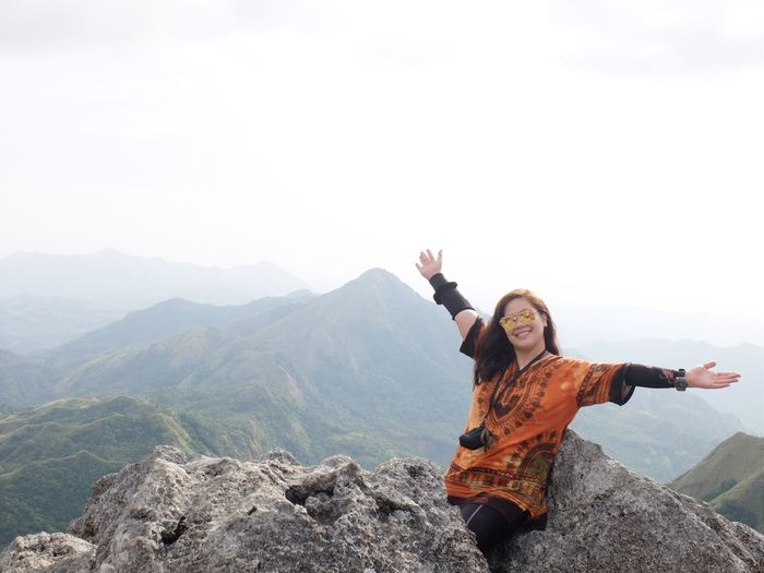 Portrait Of Smiling Young Woman With Arms Raised On Mountain Against Sky