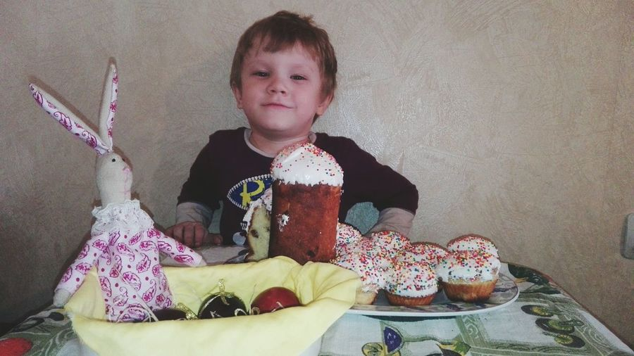 Portrait Of Boy With Dessert On Table During Easter
