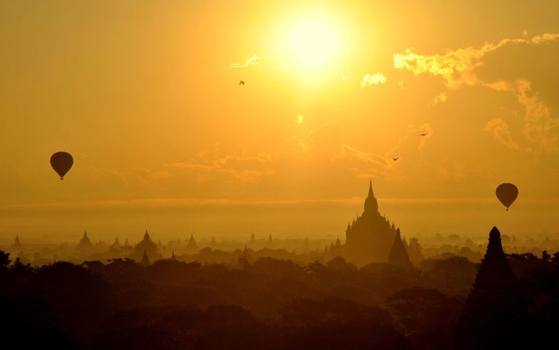 Temples against orange sky during sunrise