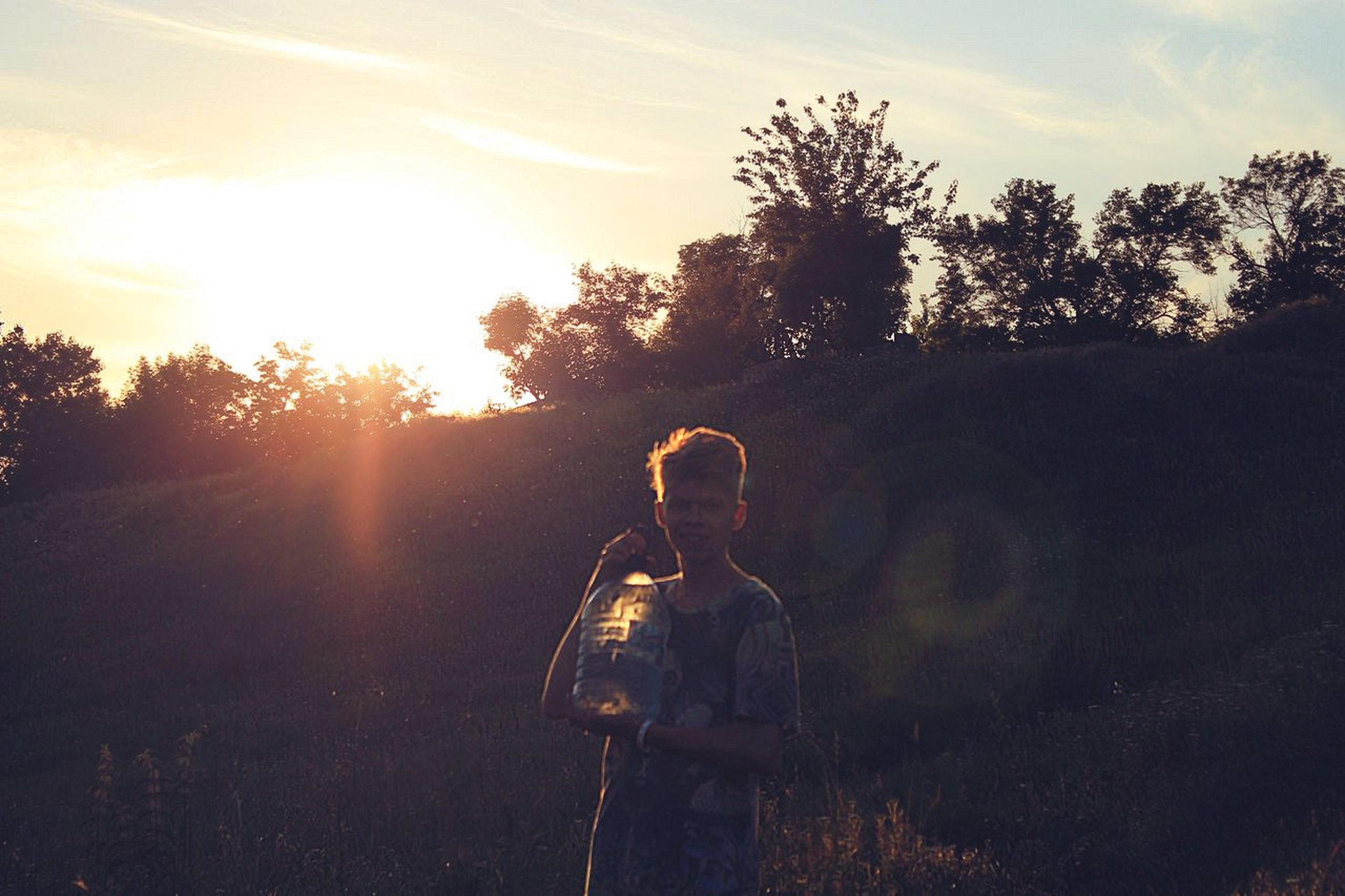 tree, sunset, silhouette, sky, sunlight, sun, leisure activity, lifestyles, outdoors, sunbeam, men, nature, holding, tranquility, technology, field, lens flare, photographing