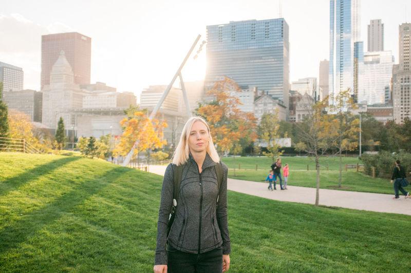 Portrait of woman at millennium park against modern buildings in city
