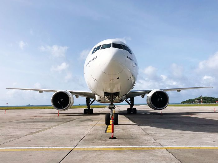 Airplane at runway against sky