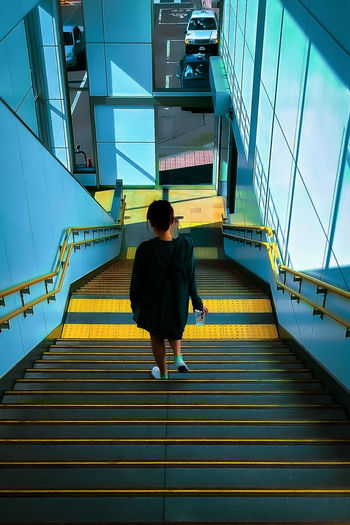 Rear view of woman walking on staircase