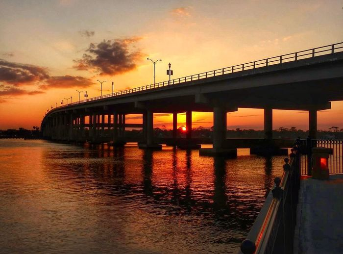 Low Angle View Of Bridge Over Calm Sea At Sunset