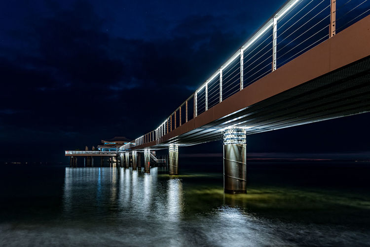 Illuminated bridge over water at night