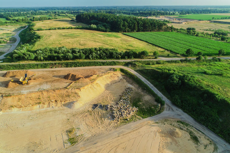 Aerial view Gravel quarrying from the air in a gravel pit Bulldozer Dismantling Excavator Industry Land Machine Transport Truck Tracks Working Background Construction Machine Dust Equipment Gravel Gravel Pit Raw Material Sand Sand Extraction Sand Pit Spilling Tracks Yellow