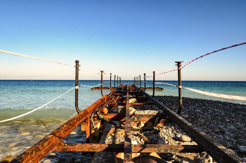 Rusty Pier Over Sea Against Clear Blue Sky