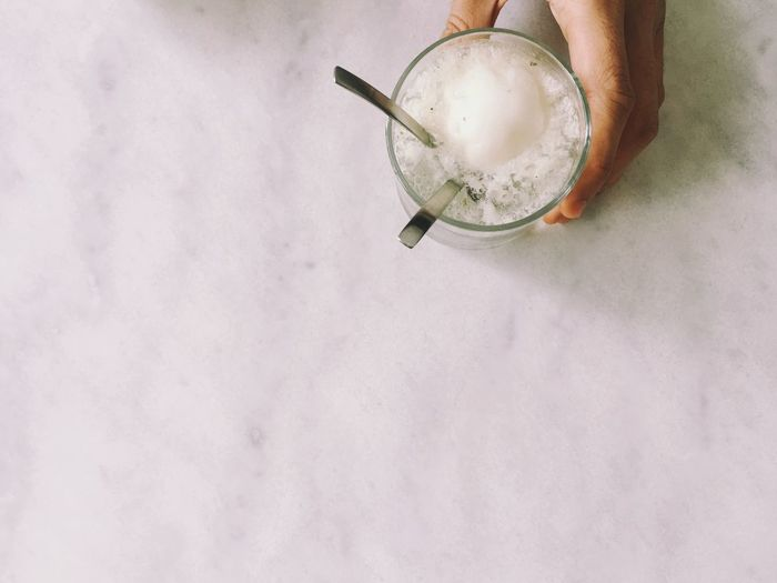 Cropped hand holding ice cream glass with spoon