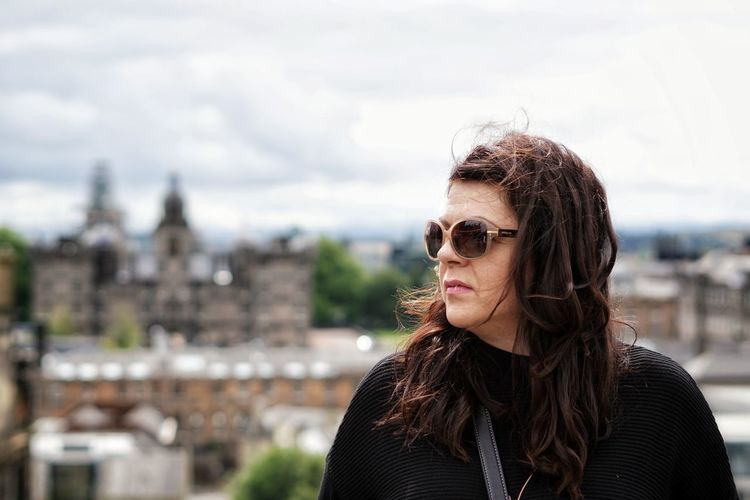 Close-up of woman wearing sunglasses looking away standing against cityscape